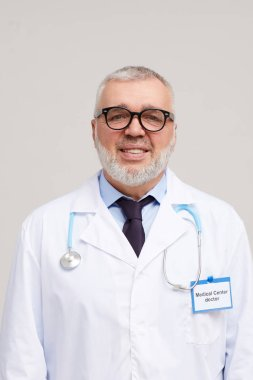 Portrait of mature doctor in eyeglasses and in white coat smiling at camera on white background