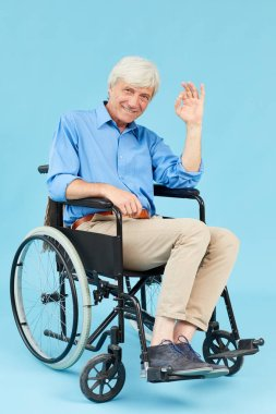 Portrait of disabled senior man sitting in wheelchair showing OK sign and smiling at camera over blue background
