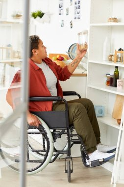 African disabled woman sitting in wheelchair near the shelves and looking at product in hand in the kitchen