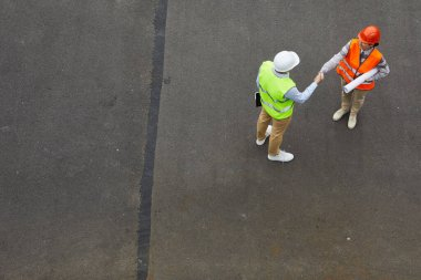 High angle view of two engineers in reflective vests and in work helmets shaking hands while they standing outdoors stock vector
