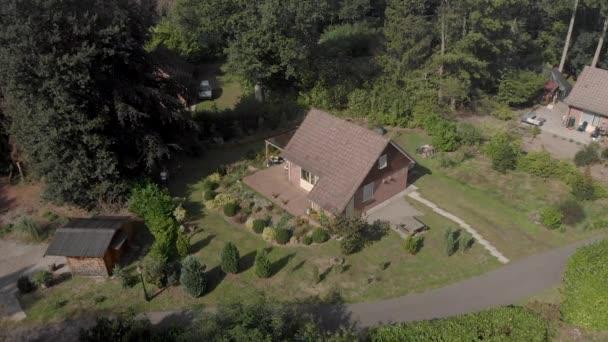 Letecký přístup k letnímu domu v rekreačním parku s terasou a navrženou zahradou v popředí