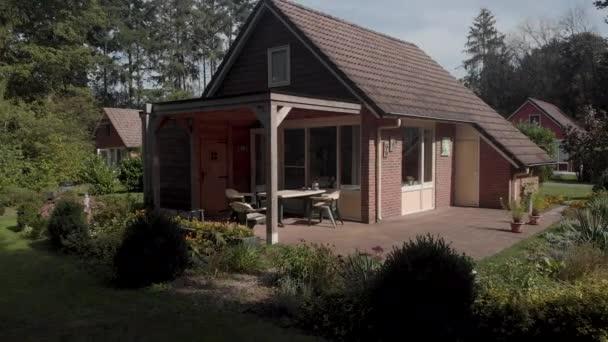 A hollandiai nyári ház légi mentése kerti tetővel és terasszal, természetes és zöld környezetben, amely az előtérben árnyékban, a kék égbolttal szemben fedi fel a növényzetet