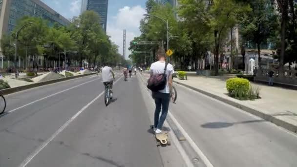Mexico City, Mexikó-június 2019: fiatalember egy gördeszka lovaglás kerékpárosok, az elmúlt években, mexikói társadalom választotta a kerékpár-és gördeszka, mint a fenntartható közlekedési eszközök.