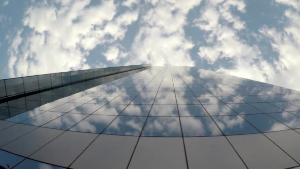 Clouds being reflected on the surface of a corporate building.