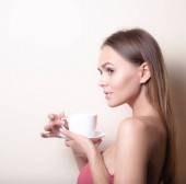 Fiatal nő élvezi egy csésze kávét. Portré nő a reggeli tea. Lemezterület másolása
