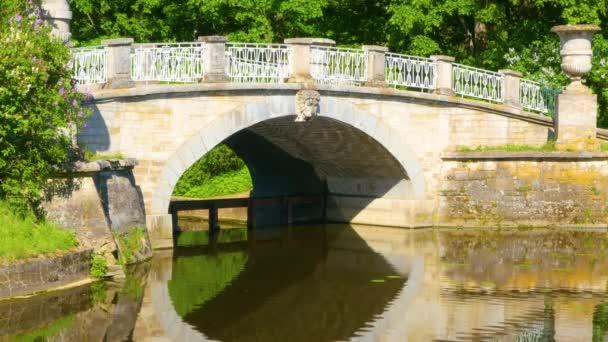 Krásný starý most v parku za jasného slunečného dne