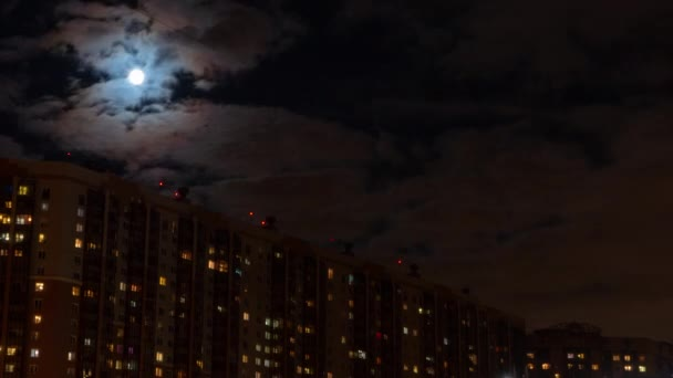 Moon flies through the clouds over a city at night. Timelapse