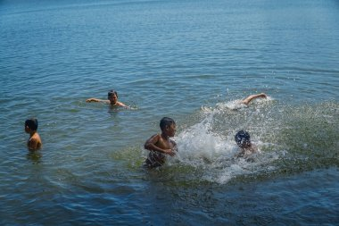 Kids are playing water in the river. Summer vacation and healthy lifestyle concept
