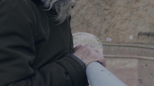 Kezében egy öreg asszony kapaszkodott a korlát egy szikla