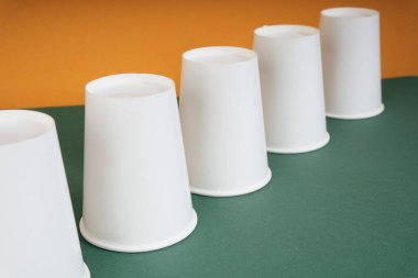 Up side down group of paper cup on green table.