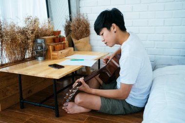 Black hair musician guy sitting at the wooden table in his bedroom and create his own song, he find the suitable note with guitar.