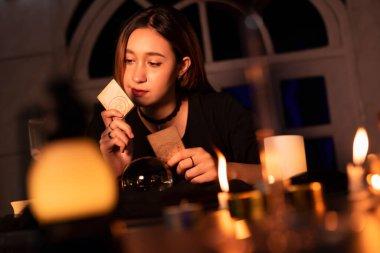 Uzun saçlı güzel kadın falcı karanlık odada geleceği tahmin etmek için tarot kartını kullanıyor..