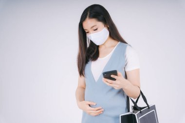 Beautiful pregnant asian woman wearing cotton mask using smartphone isolate over white background. Shopping concept.