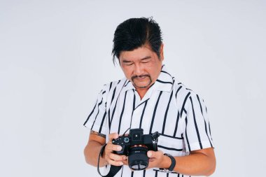 Adult asian man in white shirt as photograher with camera isolate on white background.