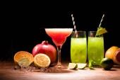 bemalte rote und grüne Alkoholgetränke in Cocktailgläsern in der Nähe von Früchten auf schwarz
