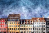 Fotografie Angemalte Häuser mit Fenstern und blauer Himmel mit Wolken