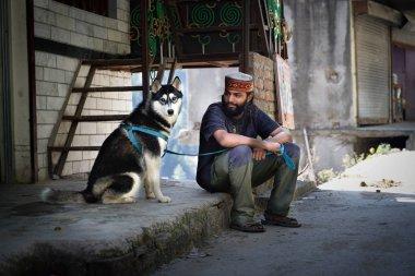 Tosh, India - October 21, 2018: indian man and husky dog