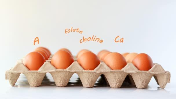 Eier auf dem Karton-Tablett mit den Nährstoffbuchstaben schweben darüber.