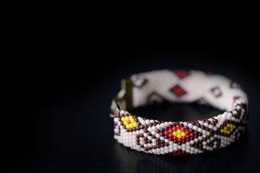 Beige bracelet with oriental pattern on a dark background close up
