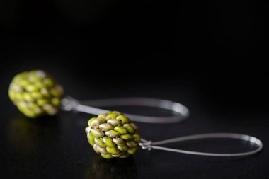 Beaded earrings green color made of superduo beads on a dark background close up