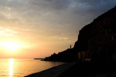 Magnificent sunrise over the sea and beautiful cloudscape on the coast of Sicily. Cefalu, Italy
