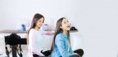 Two teen girls blogger presents beauty products, combs and transmits live video to social networks. Focus on the influencer of teenage blogger girls. Beauty blogger and vlog concept.