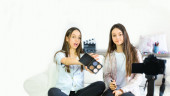Two teen girls blogger presents beauty products and transmitting live video to social networks. Focus on the influencer of teenage blogger girls. Beauty blogger and vlog concept.