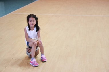 full shot of happy asian daughter taking a break and sitting on basketball in sport club with happy smiling face and looking at camera