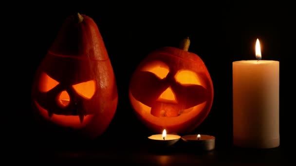 Vytesané Halloweenské dýňové světla uvnitř ohně. černé pozadí osvětlené svíčky zblízka.