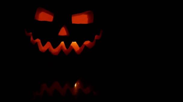 Borzalmas faragott Halloween sütőtök belsejében égő tüzet. Tükrözi. Fekete háttér.