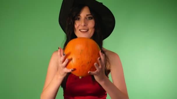 junge schöne Frau in rotem Kleid und Hexe Hut, Kürbis in den Händen. Grüner Hintergrund . Halloween-Konzept.4k
