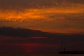 nádherný západ slunce nad mořem na pozadí siluety lodí,