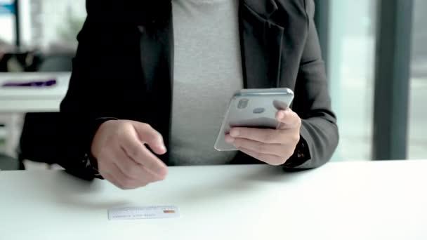 Geschäftsfrau gibt per Kreditkarte und Smartphone Geld für Online-Einkäufe aus.