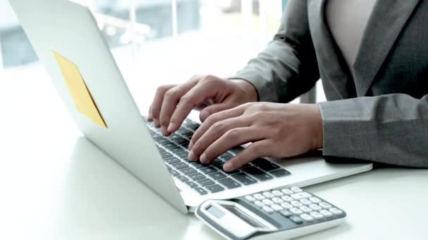 Geschäftsfrau im grauen Anzug tippt Laptop, Konzept arbeitet von zu Hause aus.