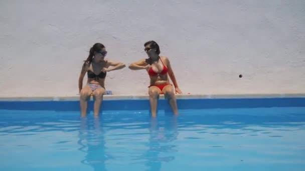 Két bikinis barna lány könyököli egymást a medencében. A világjárvány fogalma