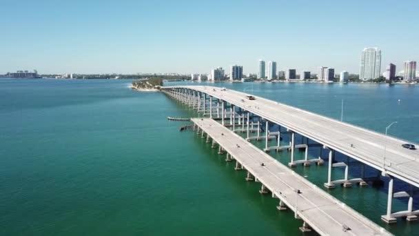 Amazing 4k aerial drone panorama shot of highway road on huge steel modern bridge across turquoise blue ocean cityscape