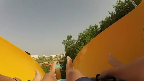 First person point of view while sliding down the aquapark colorful hydro slide with inflatable tube splashing water 4k