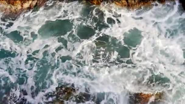 Top view of waves crashing against rocks