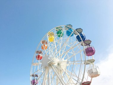 White ferris wheel with colorful cabs on a background of blue sky.
