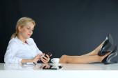 gyönyörű nyugodt szőke haj üzlet nő beszél telefonon pózol lábakkal és cipőkkel az íróasztalon az irodában