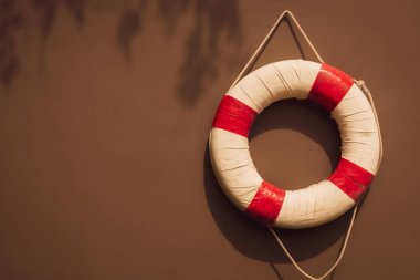 red and white safety torus or lifebuoy hanging on brown wall