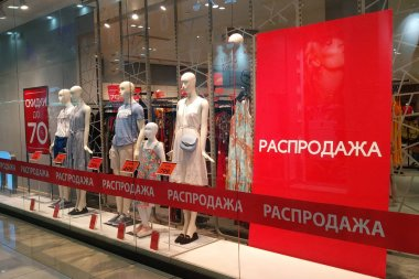Sale in a clothing store with mannequins in the shop window. Text in Russian: discounts up to 70%