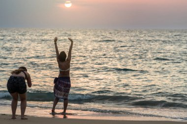 Back side of foreigner travelers taking photo of bikini women standing on the beach in the evening at sunset time. Travel and relax concept at the sea beach