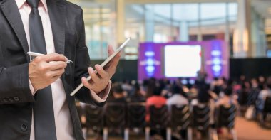 Businessman using the tablet on the Microphone over the Abstract blurred photo of conference hall or seminar room with Speakers on the stage and attendee background, Business meeting concept