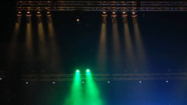 Luminous rays from concert lighting against a dark background over the projector screen, musical instrument concept