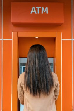 Back side of woman withdrawing the cash via ATM, business Automatic Teller Machine concept