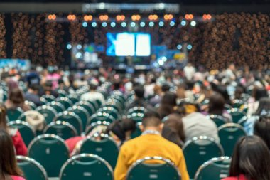 Abstract blurred photo of conference hall or seminar room in Exhibition Center with speakers on the stage and attendee background, seminar and study concept