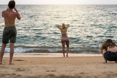 Back side of foreigner travelers taking photo of bikini women standing on the beach in the evening time after sunset. Travel and relax concept at the sea beach