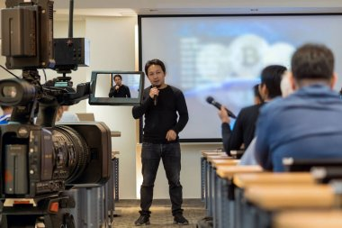 Closeup Video recording the Speaker with casual suit in front of the stage over Rear view of Audience in the conference hall or seminar meeting, event and education concept
