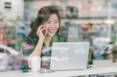 Portrait of asian businesswoman in casual suit talking and working with technology laptop in happiness action at the desk beside the glass in modern office, Business owner and entrepreneur concept